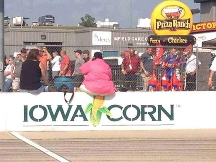 person sitting on iowa corn sign
