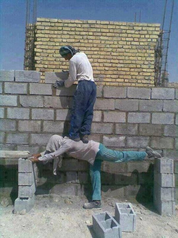 worker laying cinder blocks standing on another man