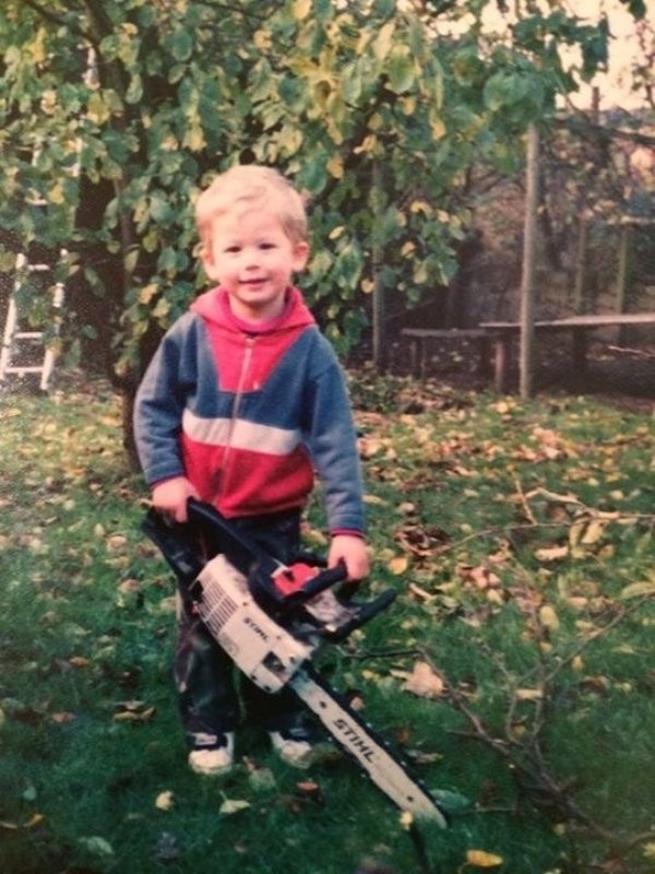 small child holding chainsaw